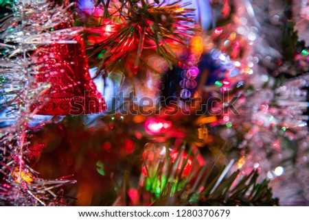 A traditional festive Christmas tree decorated with glittery and shiny tinsels, balls, ribbons, colored lights, and other beautiful objects in a horizontal image format.