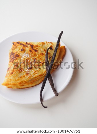 A traditional french crepe (or pancake) on a white plate, with two vanilla pods and sugar on top, white background, vertical picture