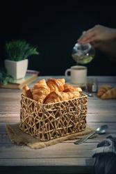 A traditional French croissants in a wooden basket, with hands pouring tea from a pot into a cup, black background with copy space.It's a buttery, flaky pastry fold with butter in multiple layers
