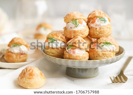 A traditional French savory choux dough cheese puff filled with fresh cheese mixed with smoked salmon in a plate decoration with dill leaf. This pastry well know as spiciality of Burgundy