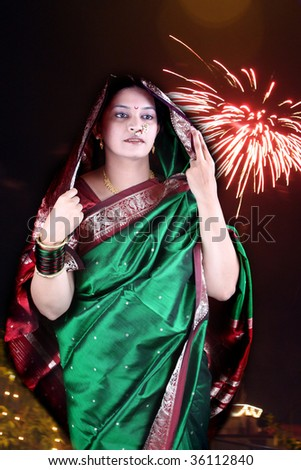 A traditional Indian woman in a green saree, on the backdrop of Diwali festival celebrations.
