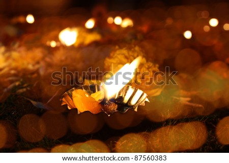 A traditional lamp lit around different lights on the festive occasion of Diwali festival in India.