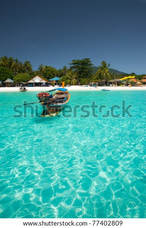 A traditional longtail boat floats in perfect crystal clear emerald blue water on the island paradise of Koh Lipe (aka Ko Lipeh), Thailand
