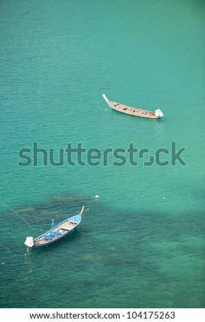 A traditional longtail boat floats in perfect crystal clear emerald blue water. Phuket, thailand