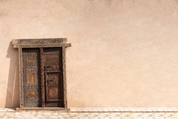 A traditional Omani Arabic wooden door, with solid wall. Copy space. Oman
