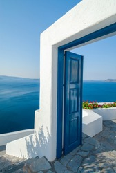 A traditional pathway with a peculiar door opening in Thira, Santorini Greece overlooking the Aegean sea.