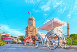 A traditional phaeton is waiting for customers by a Antalya clock tower at Republic Square - Antalya , Turkey