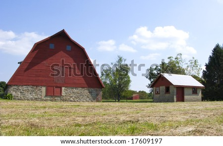 A traditional red barn and small shed