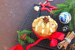 A traditional Scottish Christmas fruit mini Dundee cake with a mix of dried fruits, decorated with peeled almonds, on a black wire rack on t a brown concrete background. Christmas fruitcake recipe