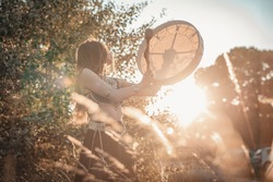 A traditional slavic shaman girl beating the drum, evoking the spirits of nature in a lovely sunset field scenery
