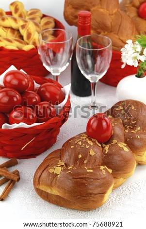 A traditional sweet brioche bread, called tsoureki, decorated with red eggs (Greek recipe) - stock photo