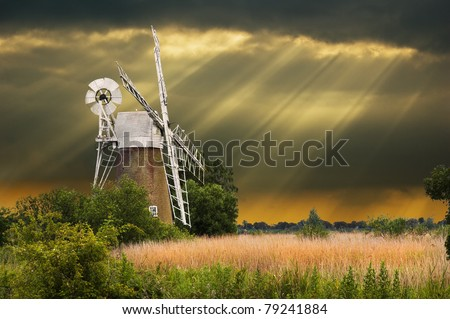 a traditional windmill in the norfolk broads, england with spectacular sun beams following a storm in the background
