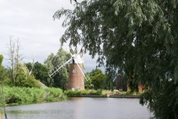 A traditional windmill (wind pump) at a bend in a tranquil river. Built on the riverbank, partially obscured by willow trees. Placid landscape in the Norfolk Broads, England, UK