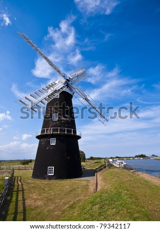 a traditional windmill wind pump on the edge of bure marsh in the norfolk broads of england on a bright sunny day