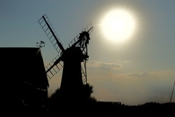 A traditional windmill (wind pump) silhouetted against a large bright low level evening sun. Shadows and darkness shroud the traditional building in the Norfolk Broads, England, UK