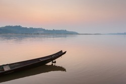 A traditional wooden boat on the Mekong Riverbank at dawn, sunrise sky reflection on surface of the river. Thailand-Laos border. Soft focus on the boat.