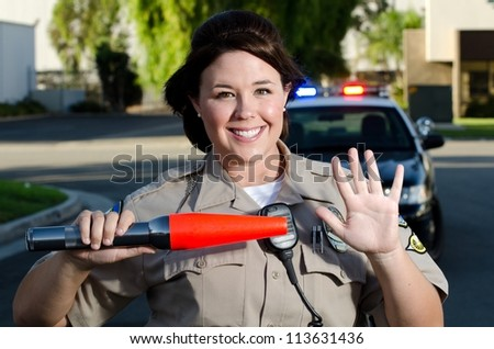 a traffic cop gives traffic a stop hand gesture while holding her flashlight.