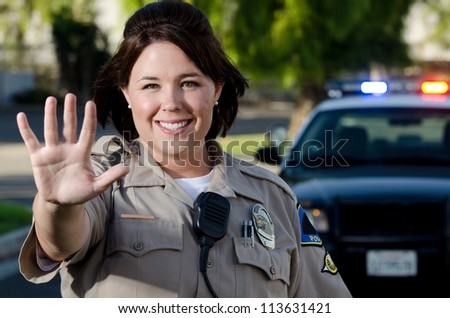 A traffic cop smiles as she holds up her hand to get cars to stop.