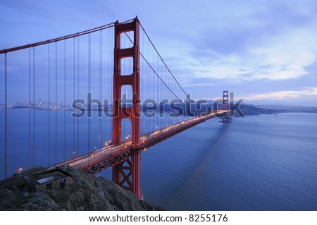A traffic flows along the glowing Golden Gate Bridge behind ruins of old fortification - stock photo