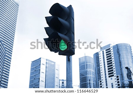 A traffic light shows green with a curving lamp post framing the background office tower. Focus is on the lights. Kuala Lumpur
