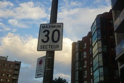 A traffic sign speed limit of 30 Km/hr in a sector with a background of a cloudy blue sky. No stop sign to the left says a bus stop from 5:30 am to 8:00 pm.