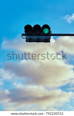 A traffic signal gives a signal against the background of a bright cloudy sky #792220552