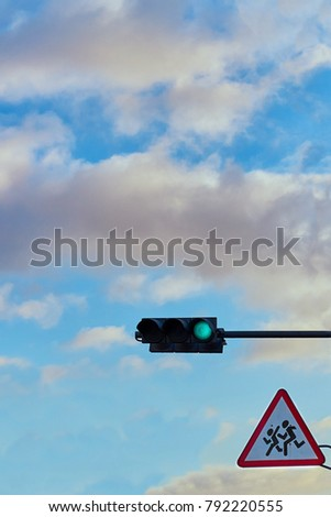 A traffic signal gives a signal against the background of a bright cloudy sky #792220555