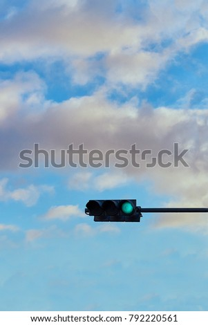A traffic signal gives a signal against the background of a bright cloudy sky #792220561