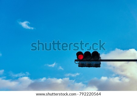 A traffic signal gives a signal against the background of a bright cloudy sky #792220564