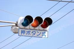 A traffic signal that changes color when pedestrians press a button. Translation: push button.