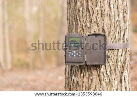 A trail camera strapped to a tree in the woods. It is open showing a photo on the screen inside. A trail camera is often used by hunters to spot deer, bear and other wildlife in the hunter's spot.