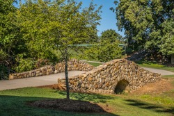 A trail in the park that has a beautiful stone arched bridge going over the creek entering into the woodlands on a bright sunny day in late summer