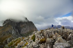 A trail runner running along a steep rocky ridge in the mountains of the Western Cape of South Africa, while a storm moves in over the mountains.