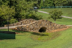 A trail with an old stone arched bridge that goes over a small creek that flows into the woodlands on a bright sunny day in summertime