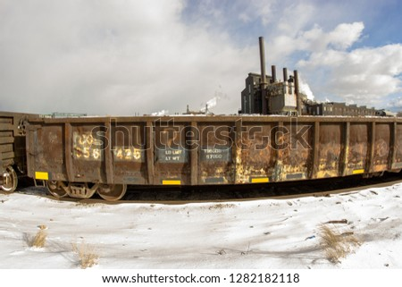 A train car in front of some industrial buildings. #1282182118