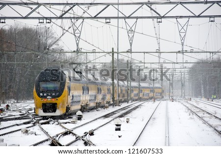 A train is arriving on a snow covered train station in the winter