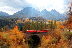A train of Rhaetian Railway traveling on a bridge thru autumn colors & Tarasp Castle perched on a hill under alpine mountains in background, in Scuol, Engadin Valley, Grisons (Graubunden), Switzerland