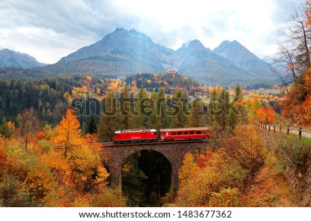 A train of Rhaetian Railway traveling on a bridge thru autumn colors & Tarasp Castle perched on a hill under alpine mountains in background, in Scuol, Engadin Valley, Grisons (Graubunden), Switzerland #1483677362