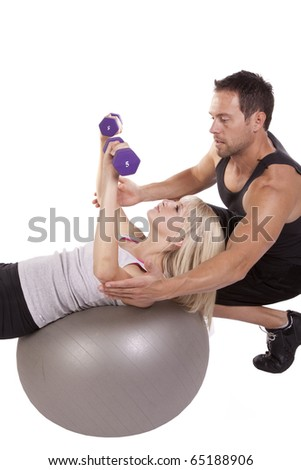 A trainer helping the woman use the weights while laying back on the ball.