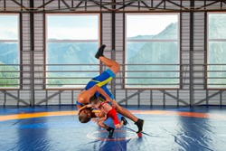 A trainer in sports wrestling tights teaches a little wrestler boy traditional throws in the style of Greco-Roman wrestling against mountains. The concept of children's sports training in martial arts