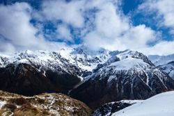 A tramp up to Temple Basin with a view of the peaks around Arthurs pass. View of snow on mountain tips and a cloudy sky.