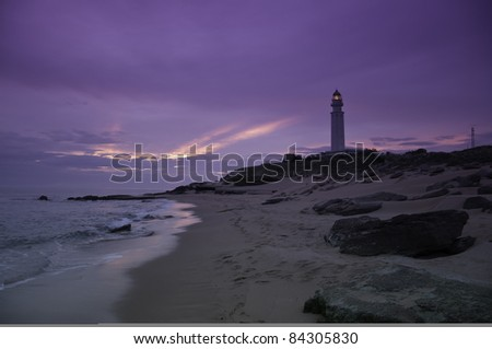 A tranquil beach with a purple sunset with a lighthouse in the background