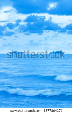 A tranquil blue sea after stormy days, scenery of tropical sea after stormy in rainy, beautiful blue clouds and soft waves at dusk. Long exposure.