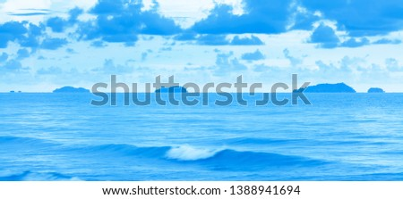 A tranquil blue sea after stormy days, scenery of tropical sea after stormy in rainy season, picturesque blue clouds and soft waves at dusk. Long exposure.