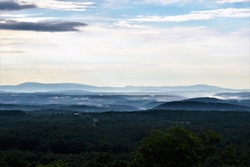 A tranquil morning begins in the Allegheny Mountains in Maryland as the sun rises and fog lifts from the valleys as seen from the Sideling Hill Welcome Center off I-68 Interstate.