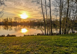 A tranquil sunset over a peaceful lake in Iphofen, Germany, dusk colors shining through trees on the bank of the body of water