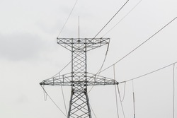 A transmission tower or power tower is a tall structure, steel lattice tower, used to support an overhead power line. Cloudy sky.