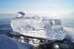 A transparent block of ice lies on the smooth ice of Lake Baikal