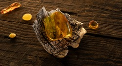 A transparent bright yellow Baltic amber stone lies on a birch bark on a natural dark weathered wooden surface. Ancient amber is healing, protection, powers, magic, good  luck charm.