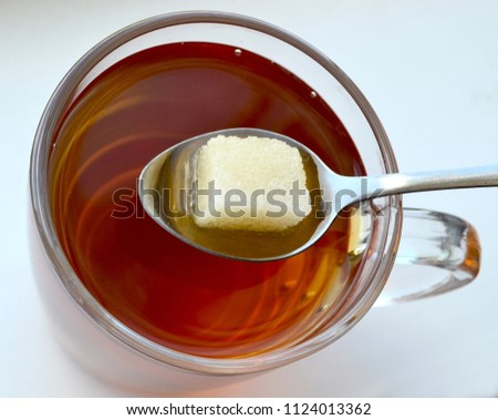 A transparent cup of black tea with a teaspoon in which a piece of sugar dissolves. Top view